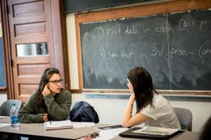 Two students talking in front of blackboard